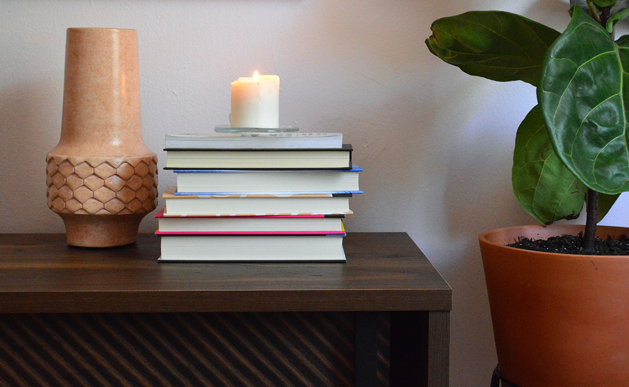Candles and books on a TV stand