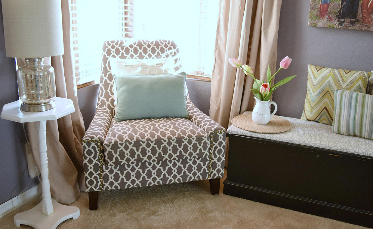 upholstered chair next to side table in the bedroom