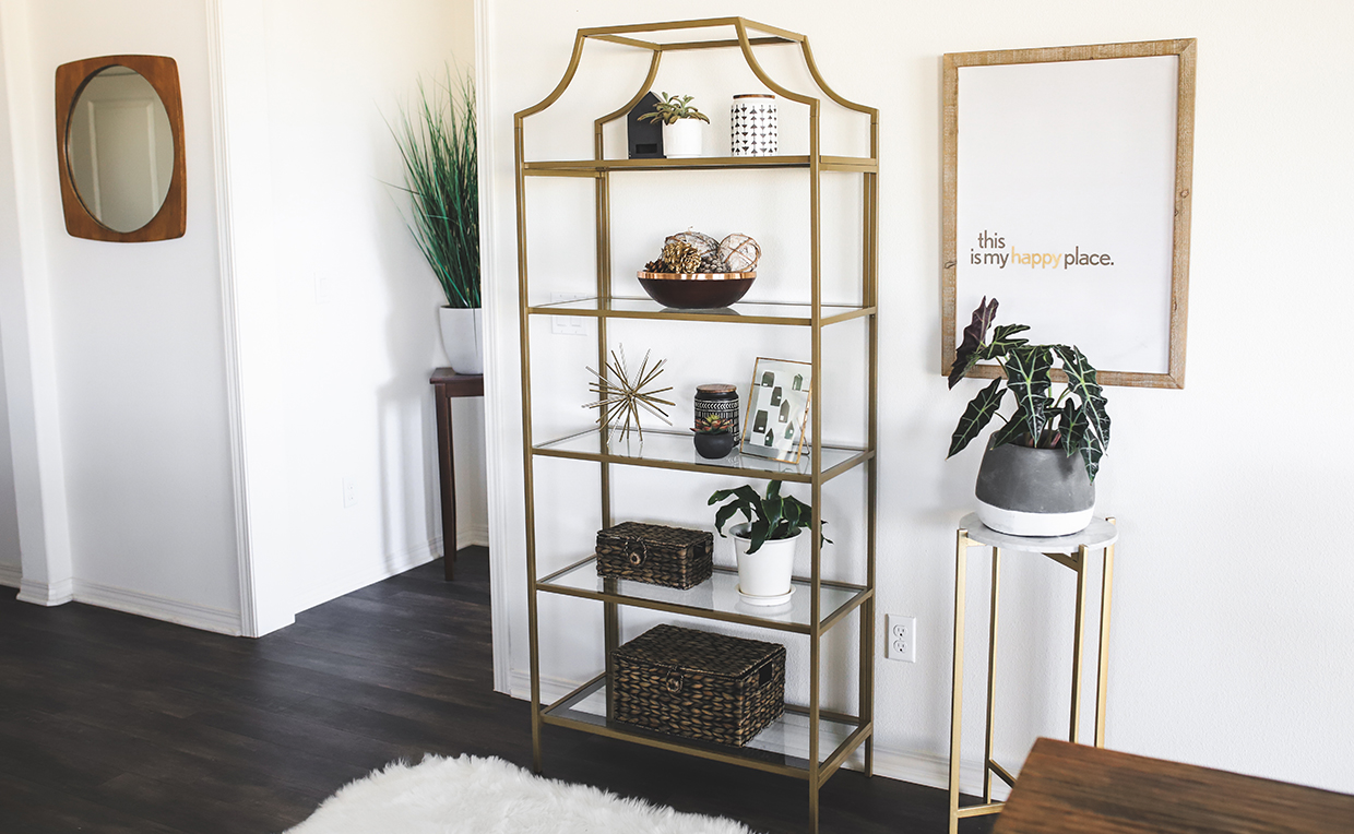 Gold metal and glass tower bookcase in dining room
