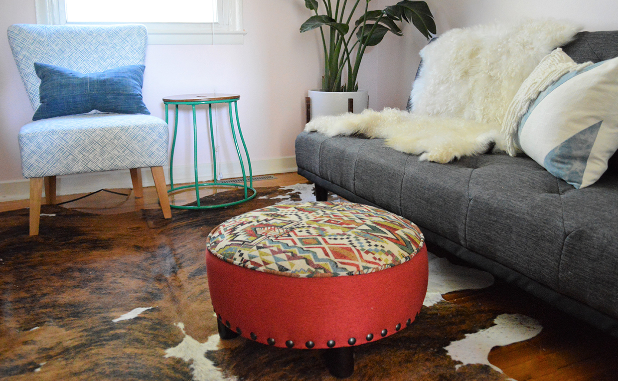 Den with couch, sheepskin blanket, chair and ottomans